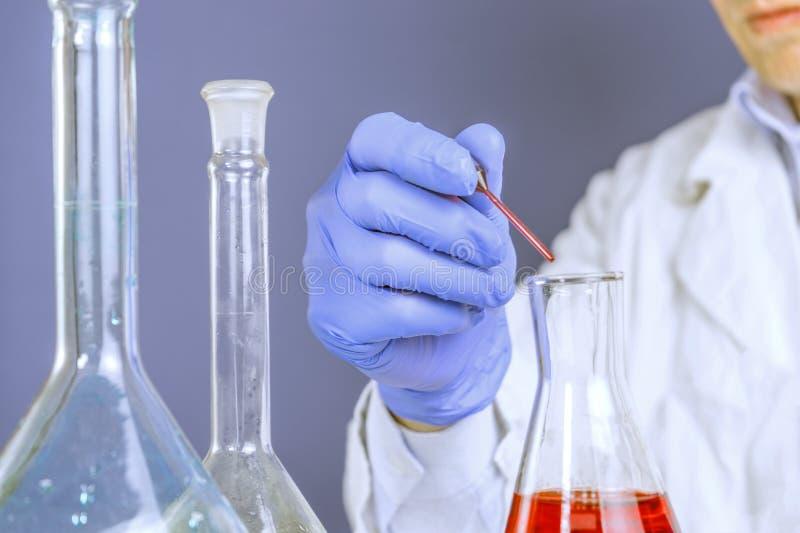 Handen van een laboratoriumtechnicus met een buis van bloedmonster en een rek met andere van de de technicusholding van het steek stock foto