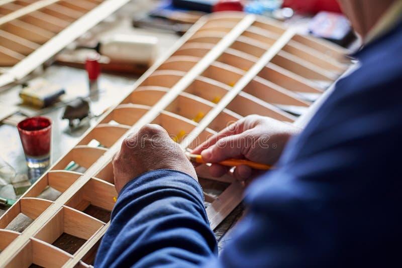 Handen van een man die de vleugel van een door radioapparatuur gecontroleerd vliegtuig maakt, de constructie van het vliegtuig stock afbeelding