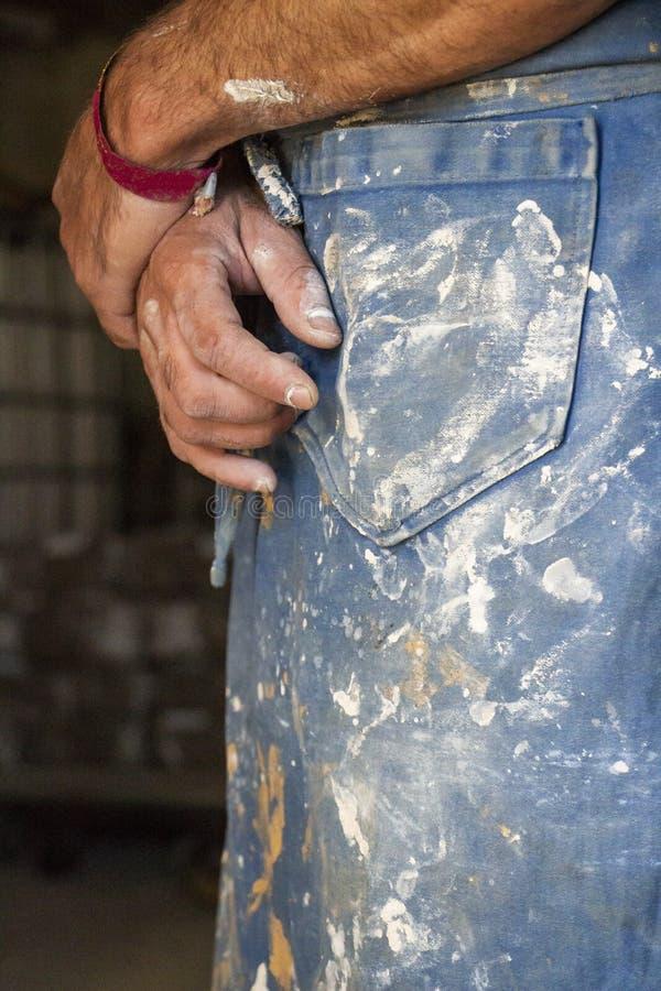 Handen van een mannelijke pottenbakker over zijn klei geploeterde schort stock foto's