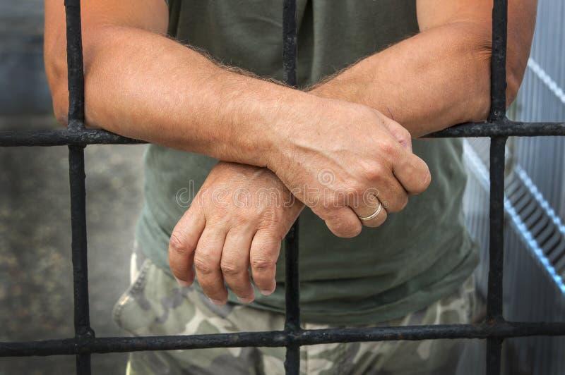 Handen van een mensen achter de tralies gevangenissen stock foto's
