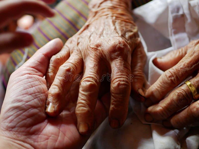 Handen van een oude harde werkende vrouw op een hand van een jongere man - geef voor bejaarde mensen stock afbeelding
