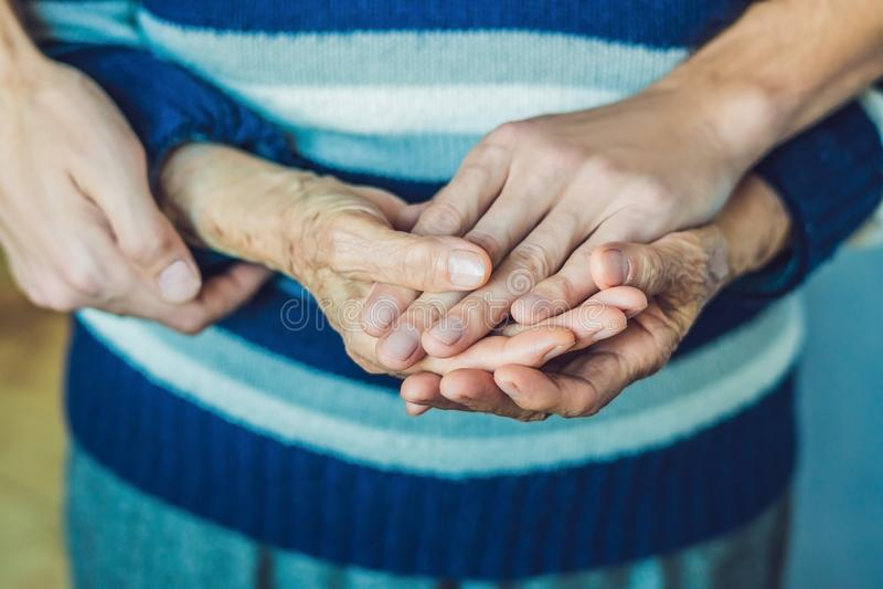 Handen van een oude vrouw en een jonge man Het geven voor de bejaarden C royalty-vrije stock afbeelding