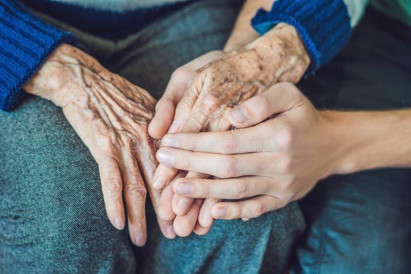 Handen van een oude vrouw en een jonge man Het geven voor de bejaarden C royalty-vrije stock fotografie