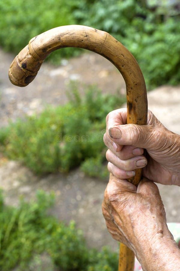 Handen van een oude vrouw met een riet stock afbeeldingen
