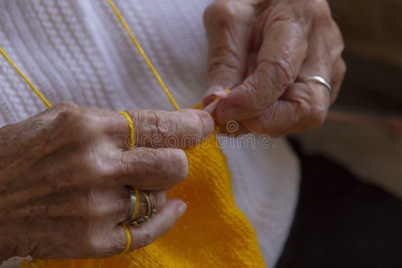 Handen van een oude vrouwenbreinaalden royalty-vrije stock fotografie