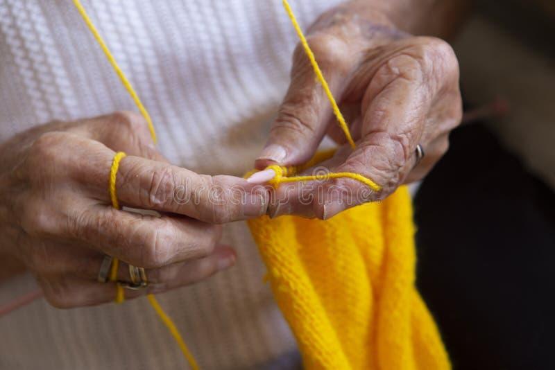 Handen van een oude vrouwenbreinaalden stock foto