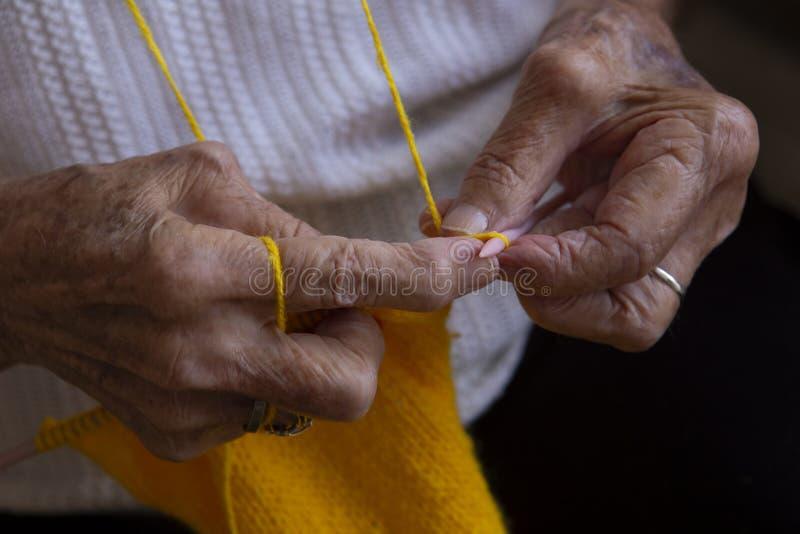 Handen van een oude vrouwenbreinaalden stock afbeelding