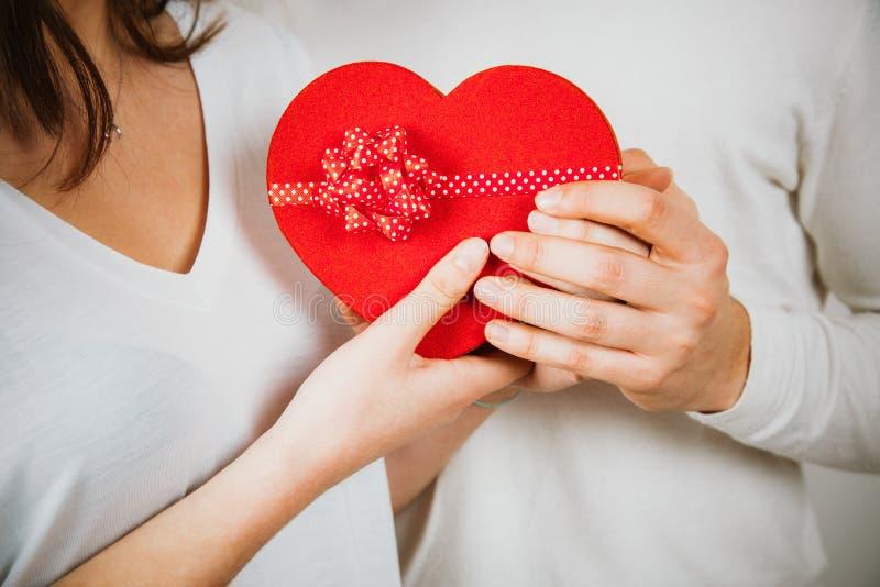 Handen van een paar die een rode hart gevormde giftdoos houden stock foto