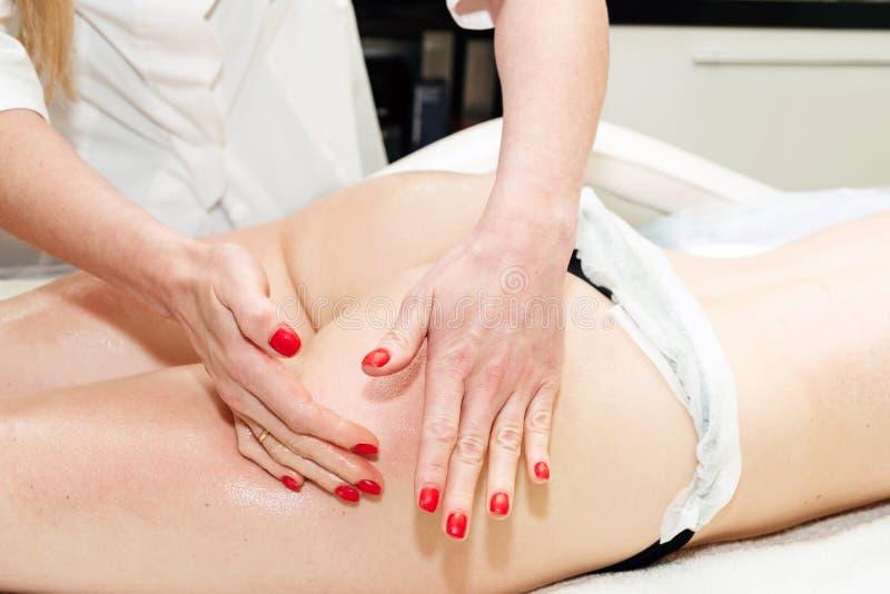 Handen van een professionele schoonheidsspecialist die anti-anti-cellulitemassage in een schoonheidskliniek maken Lichaamsverzorg royalty-vrije stock afbeelding