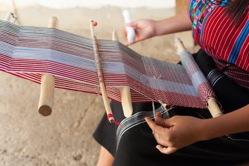 Handen van een vrouw die op een oud houten weefgetouw weven stock fotografie