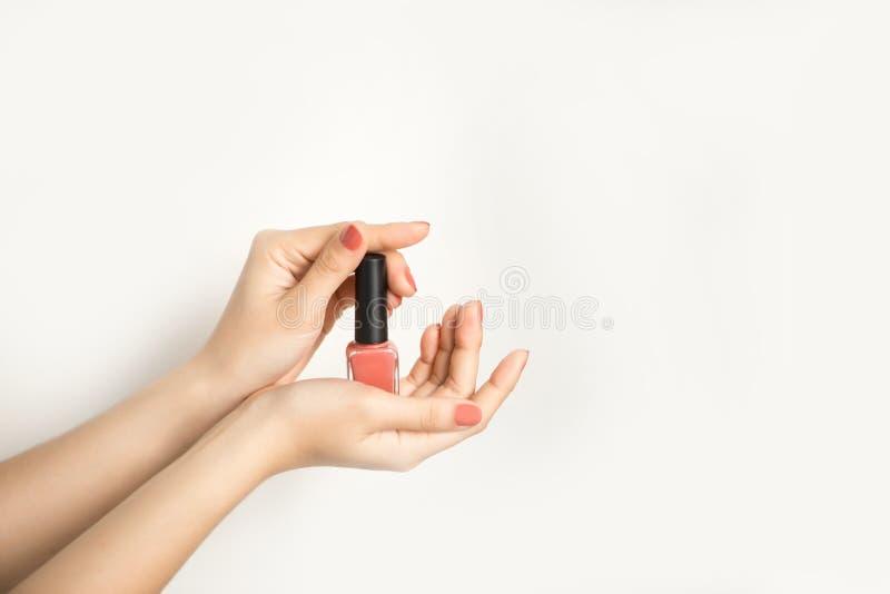 Handen van een vrouw met donkerrode manicure en nagellakfles royalty-vrije stock afbeelding