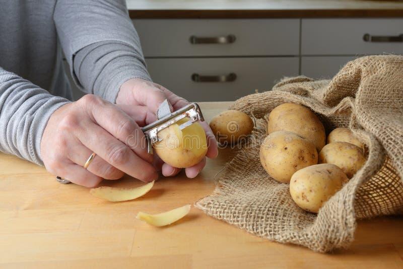 Handen van een vrouw schillen rauwe aardappelen met een oude voeler op een houten keukentafel stock afbeeldingen