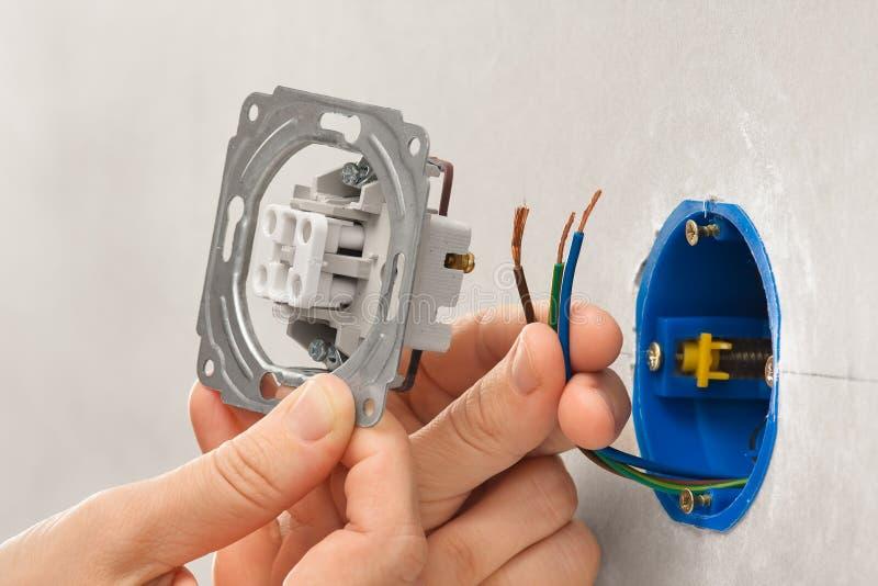 Handen van elektricien die lichte schakelaar installeren in gipsplaat wal stock foto