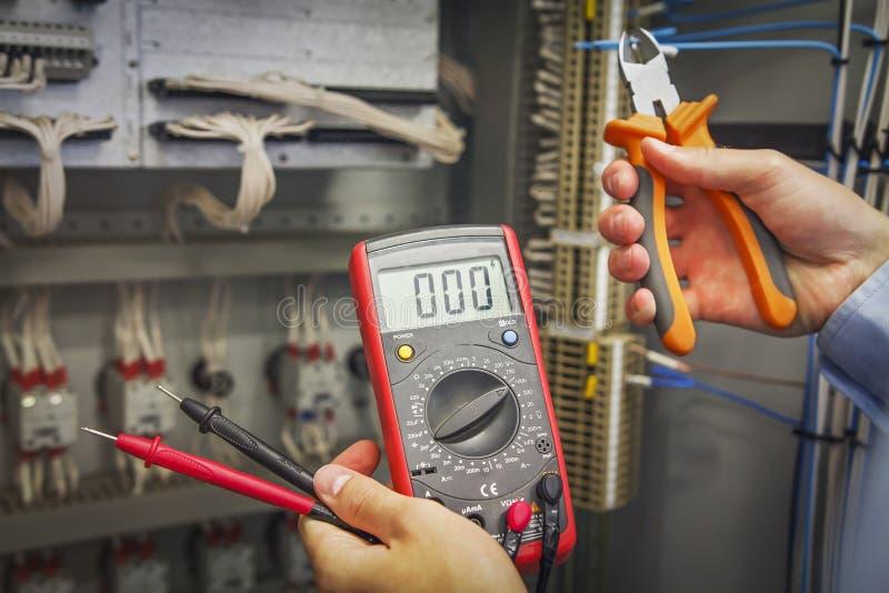 Handen van elektricien met multimeter en tangenclose-up op achtergrond van elektrisch controlekabinet voor industrieel materiaal stock foto's