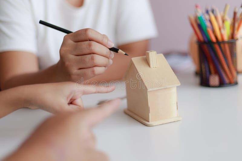 Handen van familievader moeder en daughther het richten aan droom van de blokhuis de modelmetafoor voor de huisbouw en decoratie  royalty-vrije stock afbeelding