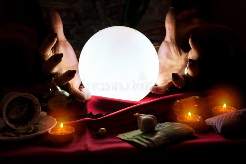 Handen van fortuinteller met kristallen bol in het midden stock foto's