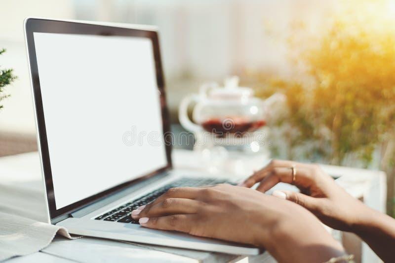 Handen van gemengde vrouw op toetsenbord van laptop royalty-vrije stock afbeeldingen