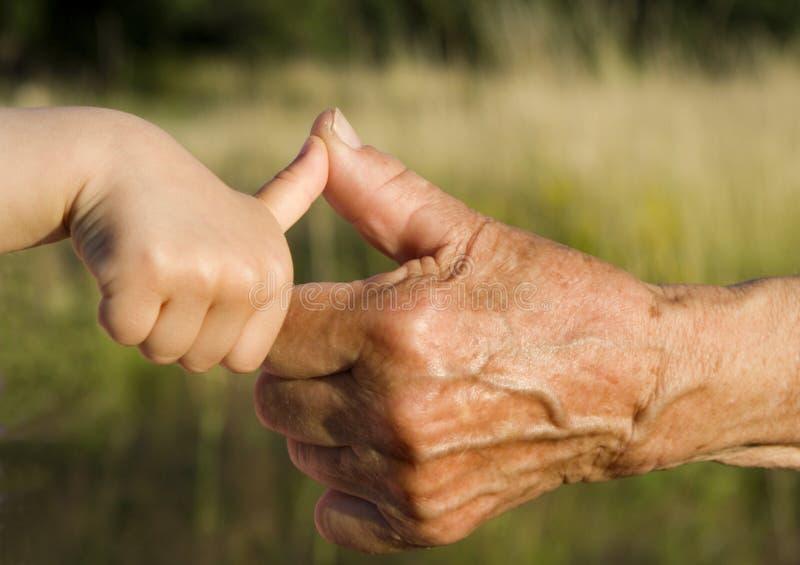 Handen van grootmoeder en kleinkind stock afbeelding