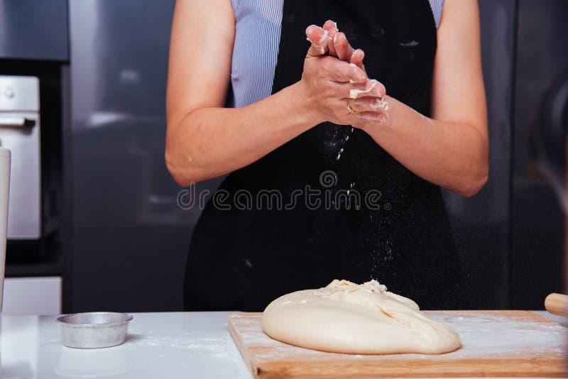 Handen van het wijfje die van de bakkersvrouw het slaan van bloemdeeg maken stock foto