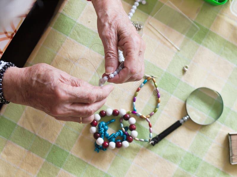 Handen van hogere vrouw die een halsband maken royalty-vrije stock afbeeldingen
