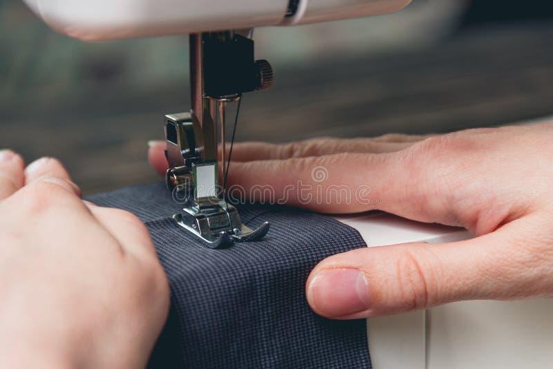 Handen van jong meisje op naaimachine stock foto's