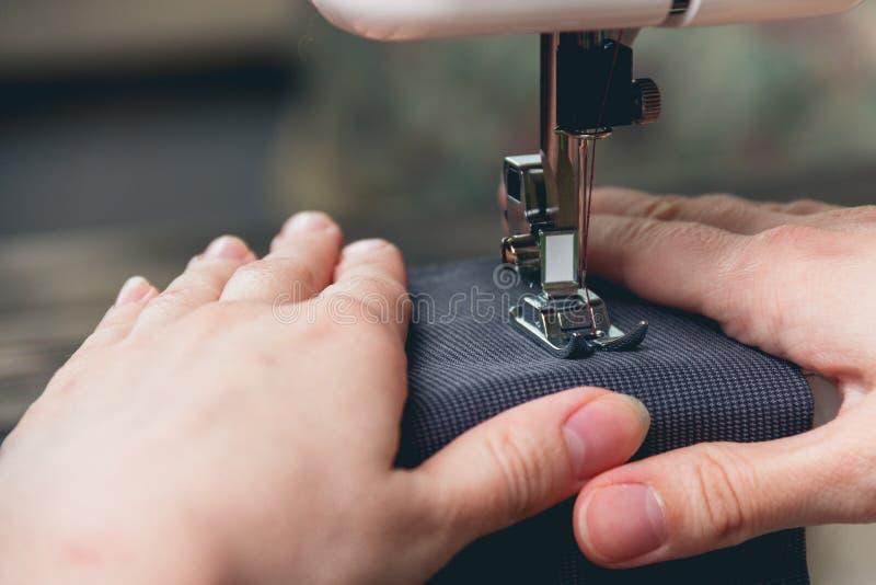 Handen van jong meisje op naaimachine stock afbeeldingen