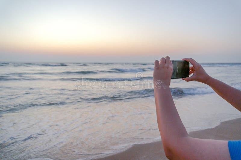 Handen van jonge Indische vrouw die een telefoon steunen om een beeld van een mooi strand in Gujarat te klikken royalty-vrije stock fotografie