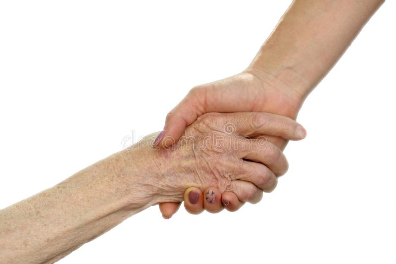 Handen van jonge volwassen en hogere vrouwen Hogere en jonge holdingshanden buiten Bejaard concept met lichte achtergrond stock afbeelding