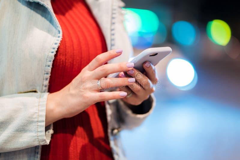 Handen van jonge vrouw die haar mobiele telefoon in nacht verlichte straat met behulp van Meisje met smartphone Het concept van d royalty-vrije stock fotografie