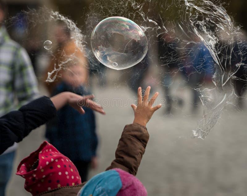 Handen van kinderen die zeepbels proberen te vernietigen stock afbeeldingen
