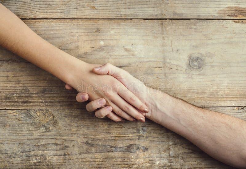 Handen van man en vrouwen het samenhouden stock foto
