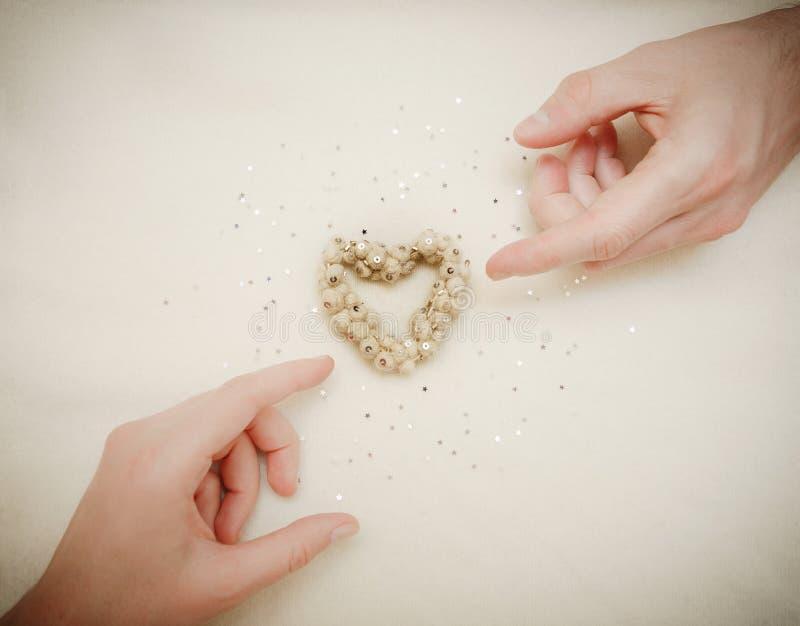 Handen van mens en vrouw door een hart wordt de verbonden dat De kaart van de uitnodiging _1 royalty-vrije stock foto's