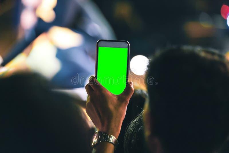Handen van mensen die mobiele smartphone met het groene scherm houden die en een beeld registreren nemen bij muziekoverleg royalty-vrije stock foto