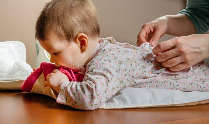 Handen van moeder die haar baby het liggen kleden stock foto's