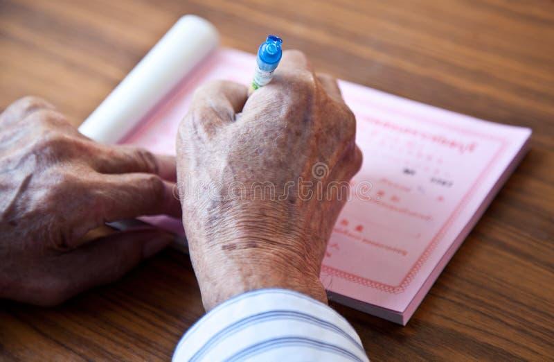Handen van olderly de mens die op bureau schrijven royalty-vrije stock fotografie