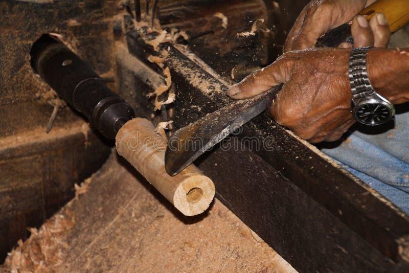 Handen van oude arbeider die een stuk van bamboehout vormen met metaalhulpmiddel in een document paraplufabriek in Chiang Mai - T royalty-vrije stock afbeelding