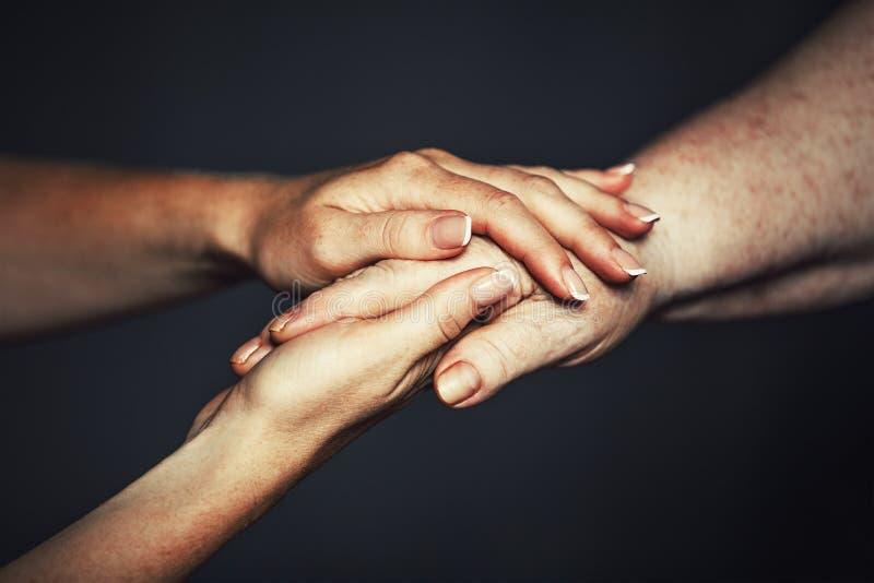 Handen van oude en jonge vrouw stock foto