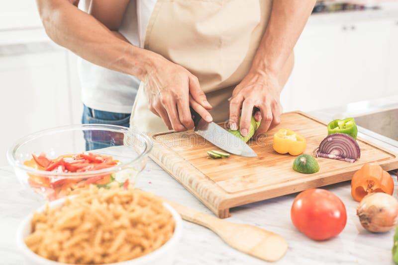 Handen van paar of minnaars die en groenten met k koken snijden royalty-vrije stock afbeeldingen