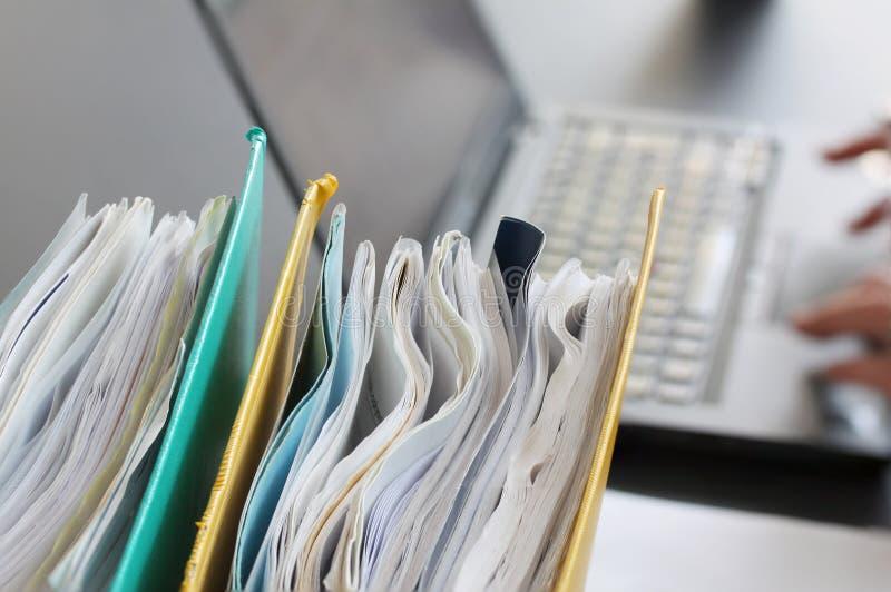Handen van persoon het typen op laptop computer met bindmiddelen met documenten in voorgrond worden gevuld die Selectieve nadruk royalty-vrije stock afbeelding