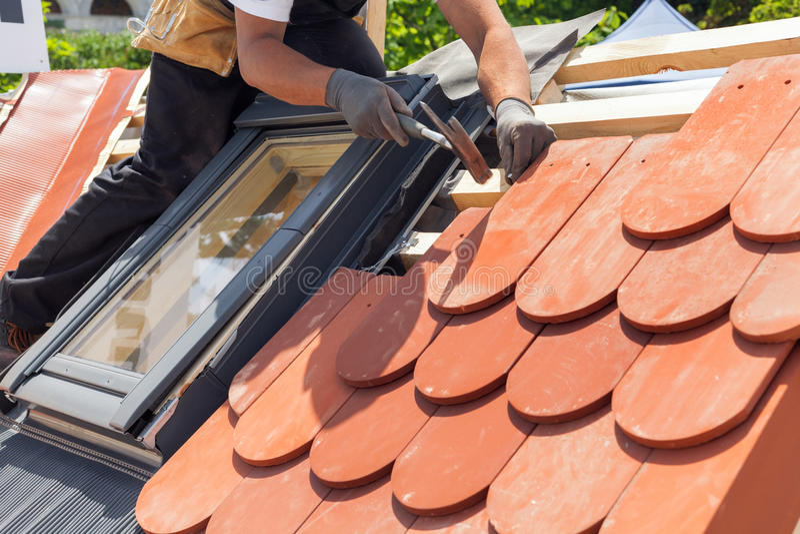 Handen van roofer die tegel op het dak leggen Het installeren van natuurlijke rode tegel die hamer gebruiken stock fotografie