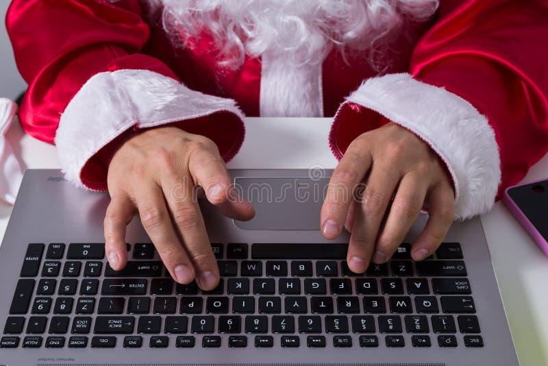 Handen van Santa Claus-het typen bij laptop toetsenbord royalty-vrije stock foto's