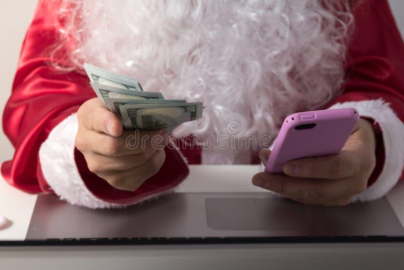 Handen van Santa Claus-holdingsgeld, dollars en smartphone royalty-vrije stock foto's