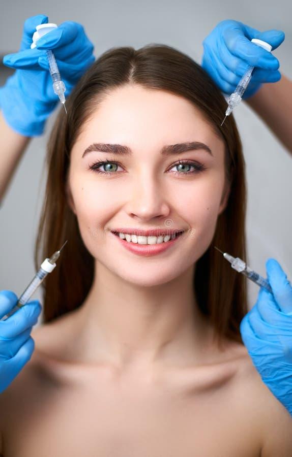 Handen van schoonheidsspecialisten die spuiten houden rond onberispelijk vrouwengezicht klaar voor injectie in de kosmetiekklinie royalty-vrije stock foto's
