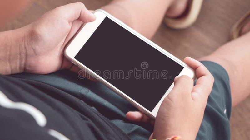 Handen van smartphone van de jongensholding ter beschikking met het zwarte scherm royalty-vrije stock afbeelding