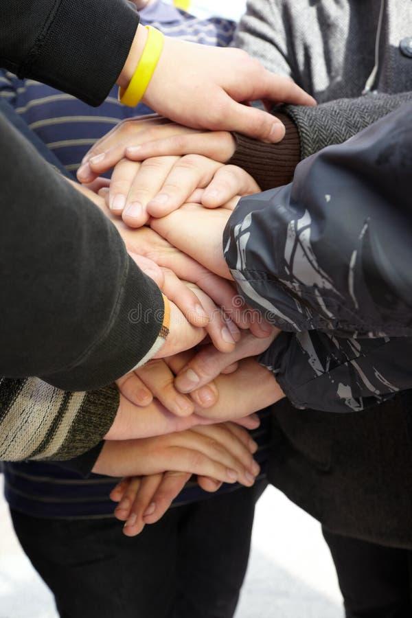 Handen van tienerjaren samen. unie royalty-vrije stock afbeelding