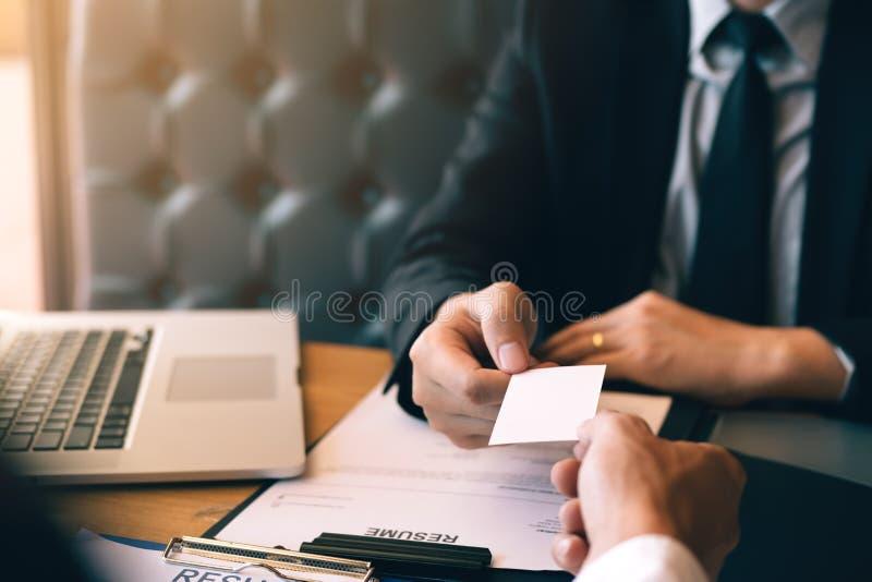 Handen van twee bedrijfsmensen die in bureauruimte zitten die en leeg adreskaartje geven nemen stock foto's
