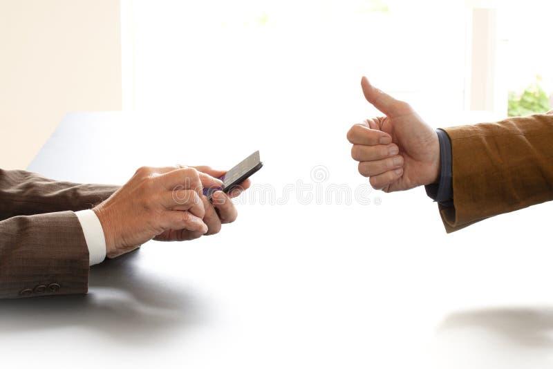 Handen van twee zakenlieden in gesprek door een bureau Één die op een mobiele telefoon texting Andere geeft o.k. tekenduimen op N stock foto's