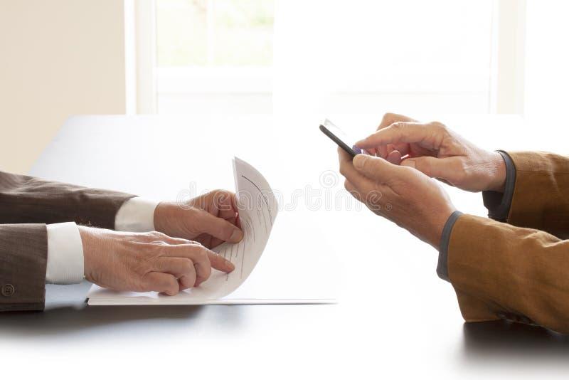 Handen van twee zakenlieden in gesprek door een bureau Één die in sommige documenten en andere het texting op een celtelefoon ric royalty-vrije stock afbeelding
