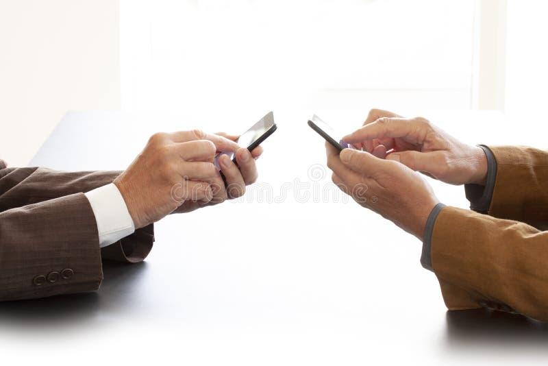 Handen van twee zakenlieden in gesprek door een bureau Beide mensen texting op een cel telefoneert Het onderhandelen zaken of een royalty-vrije stock afbeelding