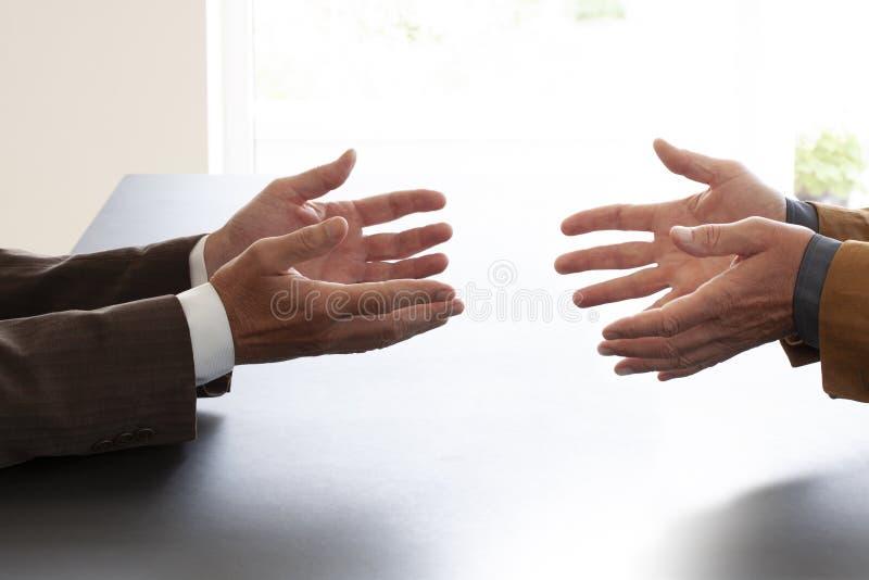 Handen van twee zakenlieden in gesprek door een bureau Het onderhandelen zaken of een baangesprek - Beeld stock afbeeldingen